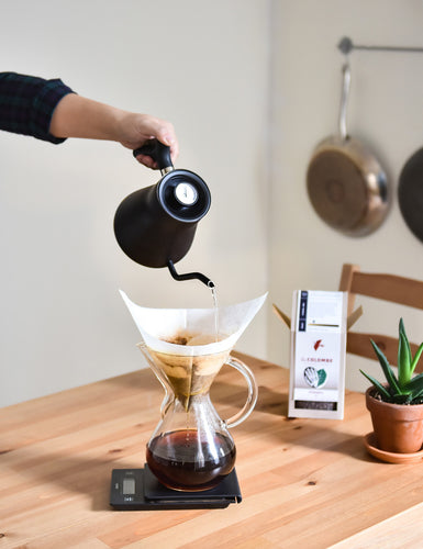 Image of someone pouring hot water from a Stagg Kettle into a Chemex Coffeemaker on a Hario Scale.