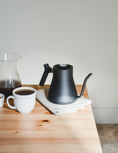 Angeled shot of a Stagg Kettle with a cup of coffee.