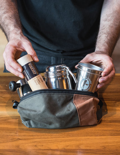 Image of someone puting a Coffee Survivor Kit into a hiking pouch.