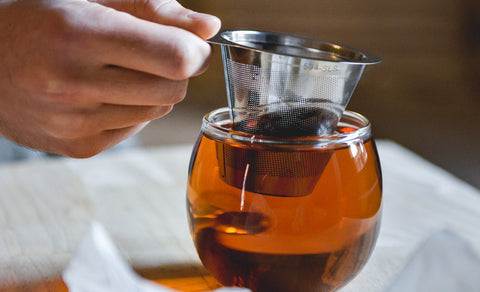 Close-up shot of someone brewing tea using the ForLife Brew-In-Cup.