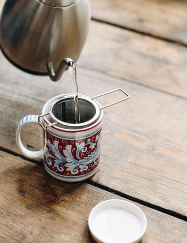Angled shot of someone pouring hot water through the ForLife Tea Infuser into a mug.