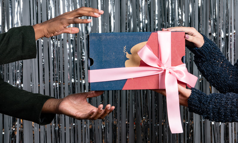 Hands gifting a box of La Colombe wrapped in a bow.