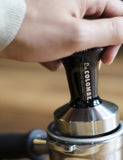 Another close-up shot of someone using a La Colombe X Reg Barber Tamper.