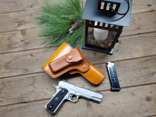 A naturally colored leather holster for the 1911, full coverage lid and mag pouch laying next to a candle lantern and pine boughs