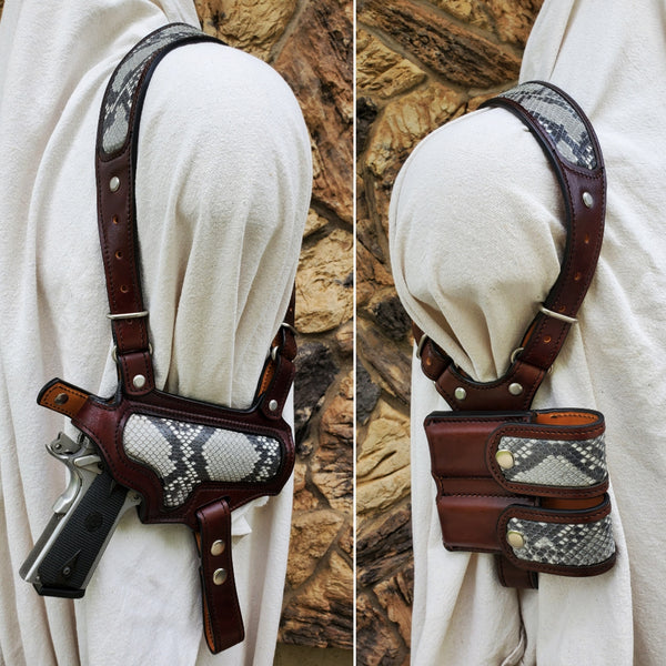Dark brown leather shoulder holster for 1911 with gray python inlay and double magazine pouch hanging on a mannequin draped in white canvas