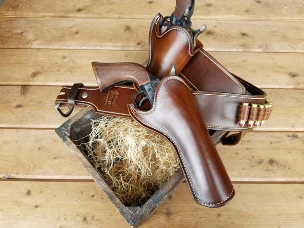 Lustrous rich brown holster and gunbelt set modeled after Josh Faraday's rig from Magnificent 7 sitting atop a wooden floor and crate.
