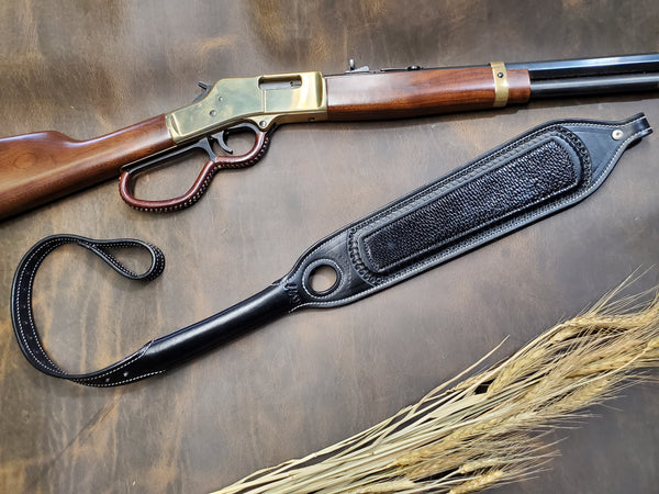Black leather rifle sling with a black beaver tail overlay and tooled edges lays on a rustic brown background next to a Henry rifle and small bundle of wheat