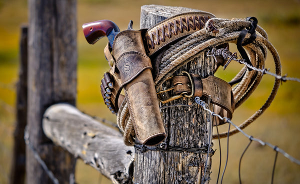 beautiful rustic western gun rig on a weathered fence post