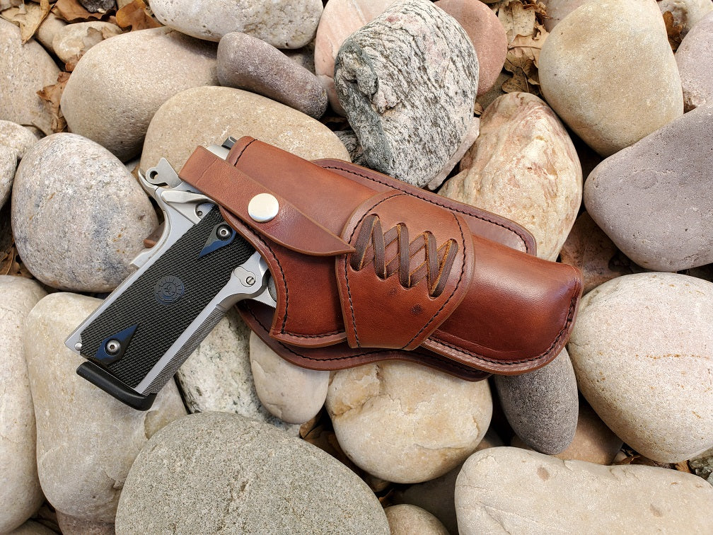 Western style 1911 holster in full grain leather and a laced collar sitting on smooth river rock.