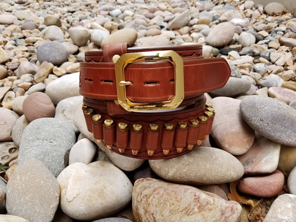 Brown leather cowboy gun belt with a bright brass buckle coiled on smooth gray river rocks