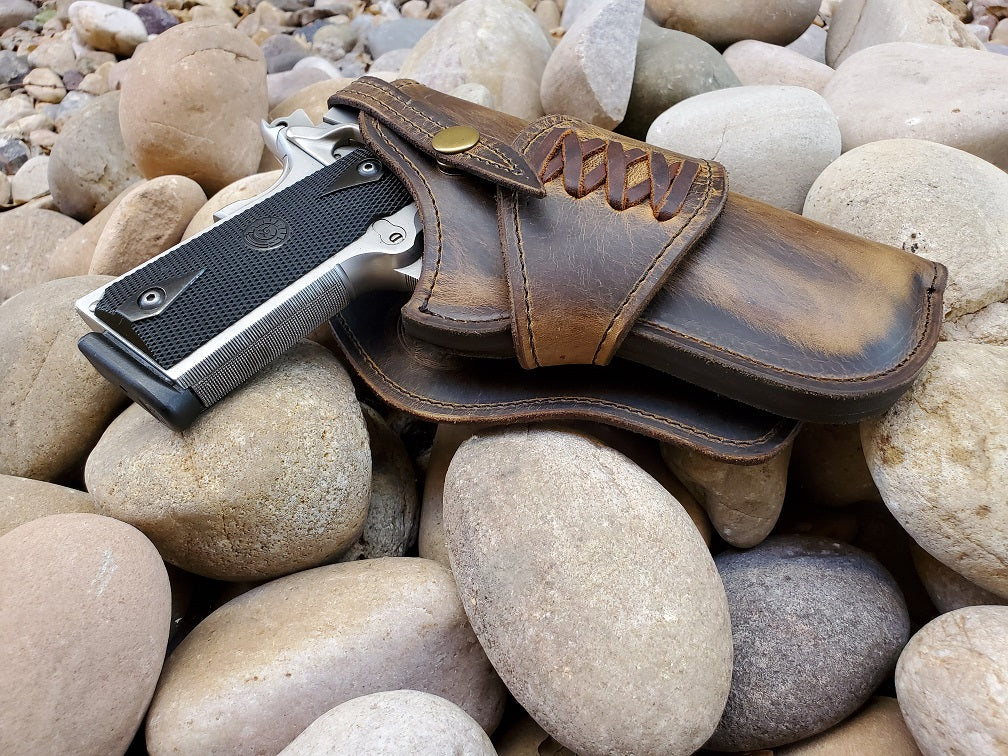 Rustic leather holster for 1911 sitting on river rocks