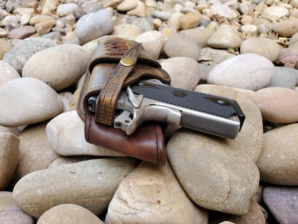 Rear view of a leather 1911 holster. Veg tan lined with a brown rustic exterior and snap retention.