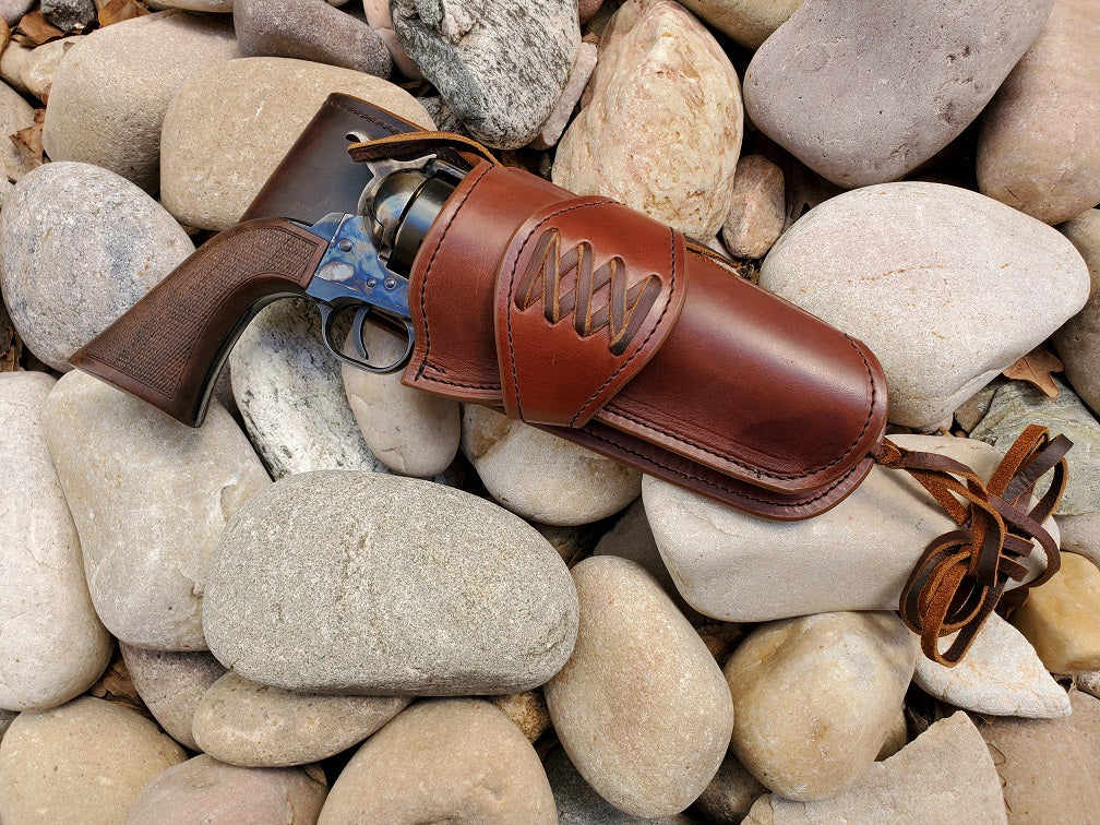 Beautiful smooth brown leather single action holster with a laced collar and medium drop sitting on smooth river rocks. At the bottom of the holster is a bundle of leather lace for a leg tie.