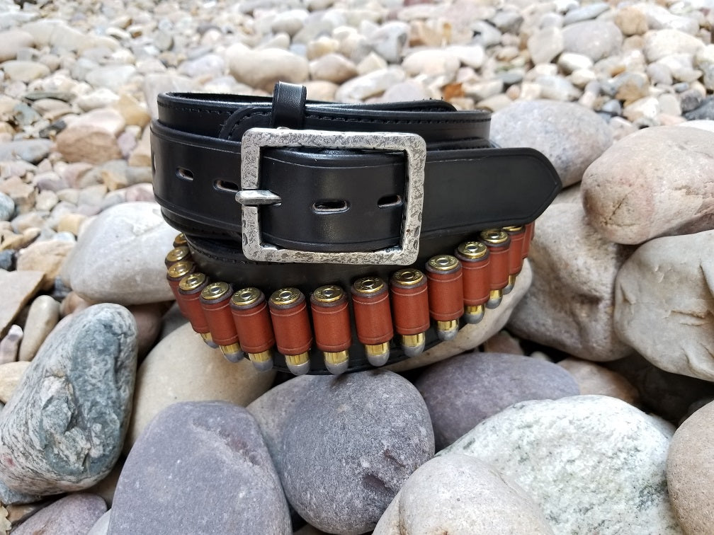 Black cowboy belt with hammered buckle coiled around itself sitting on smooth river rocks.