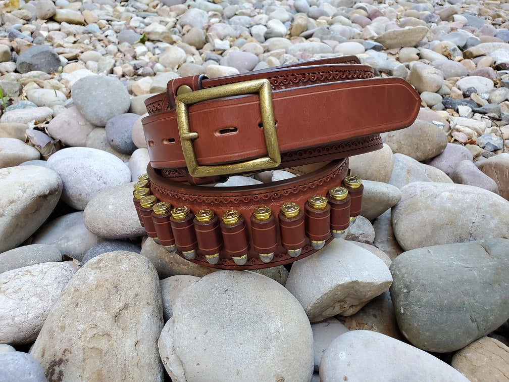 Closeup of a loaded western gun belt with fancy border tooling and antique brass center bar buckle.