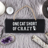 Black hanging wall sign featuring the text 'One Cat Short of Crazy'. Would make a fun gift for any cat lover.