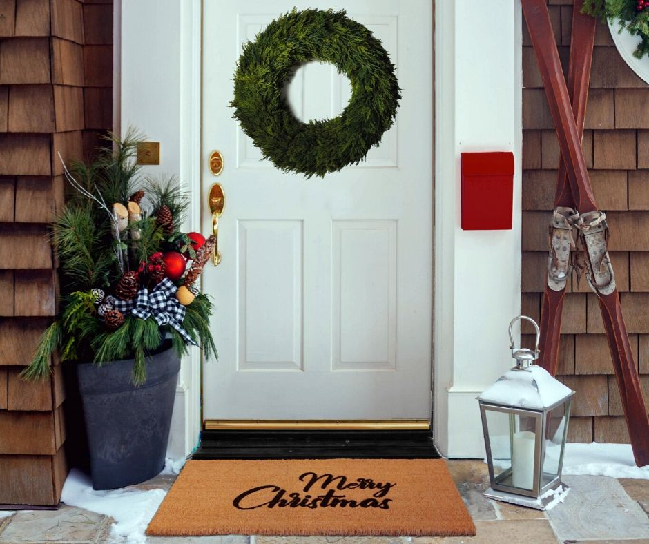 Cedar shake front porch. Evergreen wreath on white door with holiday planter, merry christmas mat and silver bell lantern
