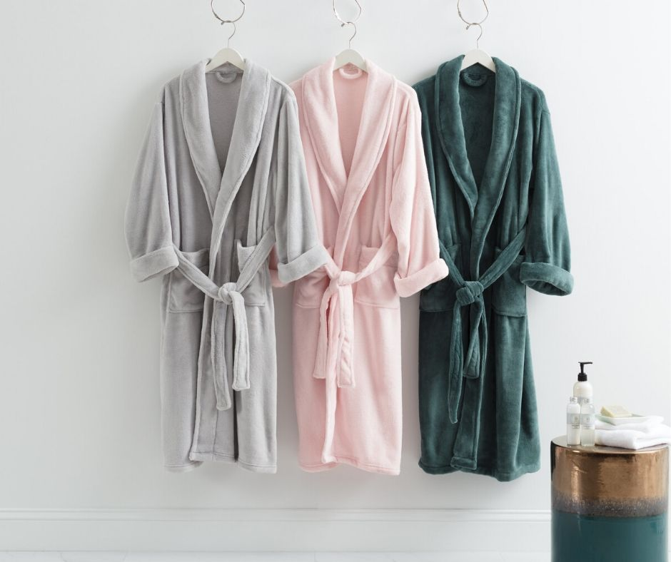 A white, rose and dark green robes hanging on a white wall