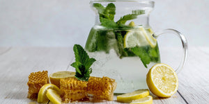 Image of water in a pitcher next to lemons, honey and mint