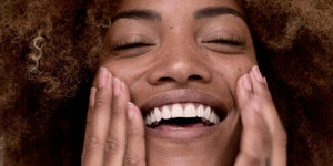 Image of woman smiling and touching her face
