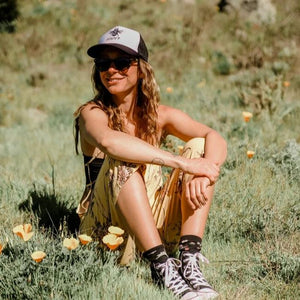 Bee happy mesh trucker hat in black/white lifestyle image of woman wearing