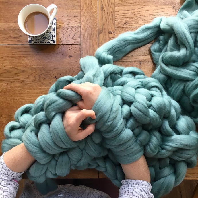Arms giant knitting a light teal blanket with a cup of tea to the side