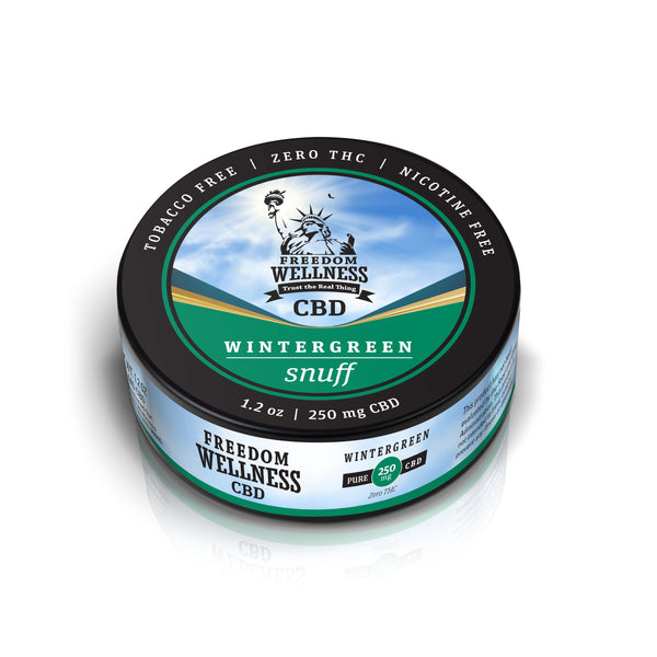 Angled close up of a Freedom Wellness CBD wintergreen flavor organic snuff can with top and front labels showing and a total content of 250mg CBD. Black 1.2oz can.
