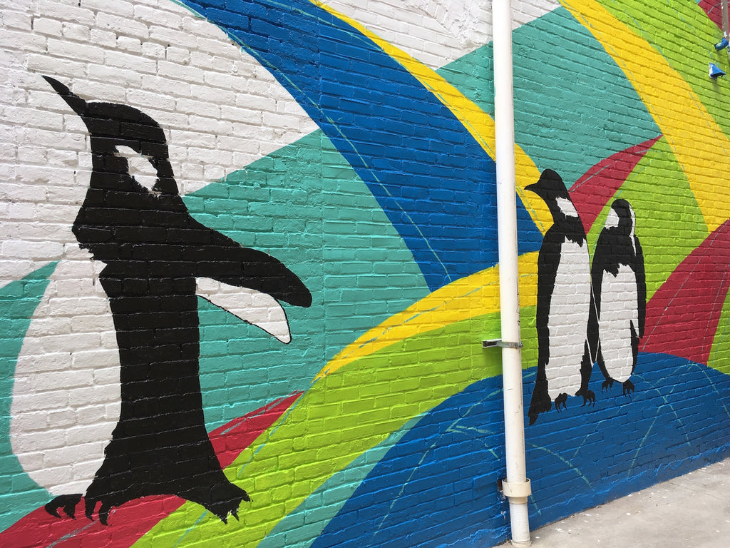 A custom exterior mural of penguins on a brick wall
