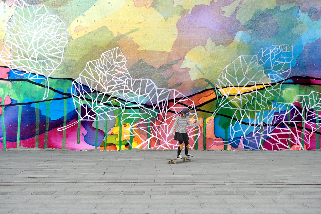 A girl skateboards in front of custom exterior mural with bright colors and plant leaves