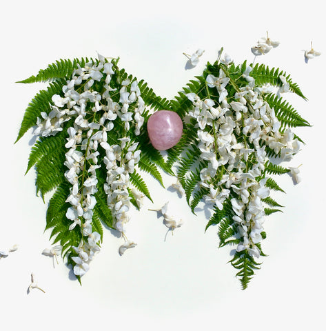 Fallen flowers are scattered across blooming Wisteria shaped into lungs around a rose quartz heart.