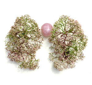 Delicate clusters of tiny white blooms form lung shapes  around my rose quartz heart