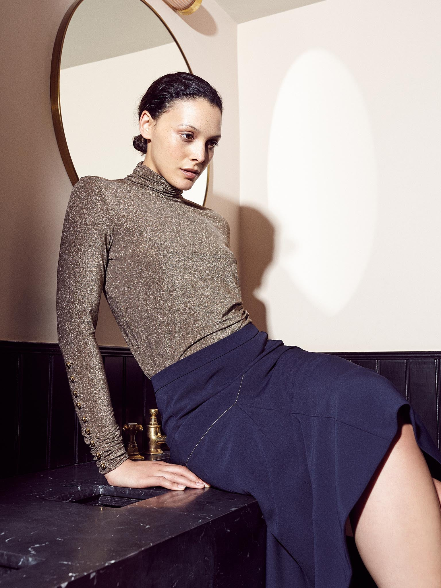 Model wearing gold lurex turtle neck with gold buttons and asymmetrical navy skirt with gold thread detail