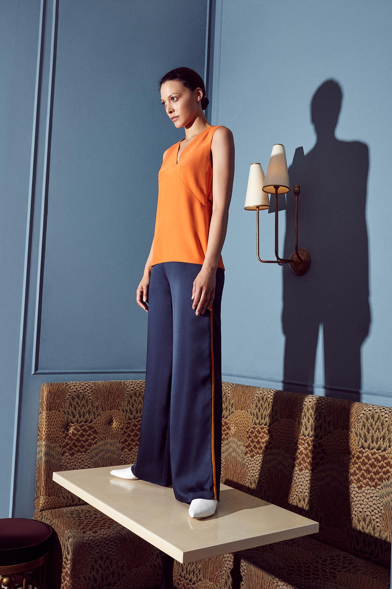 Model wearing orange silk sleeveless top and navy sating wide leg trousers