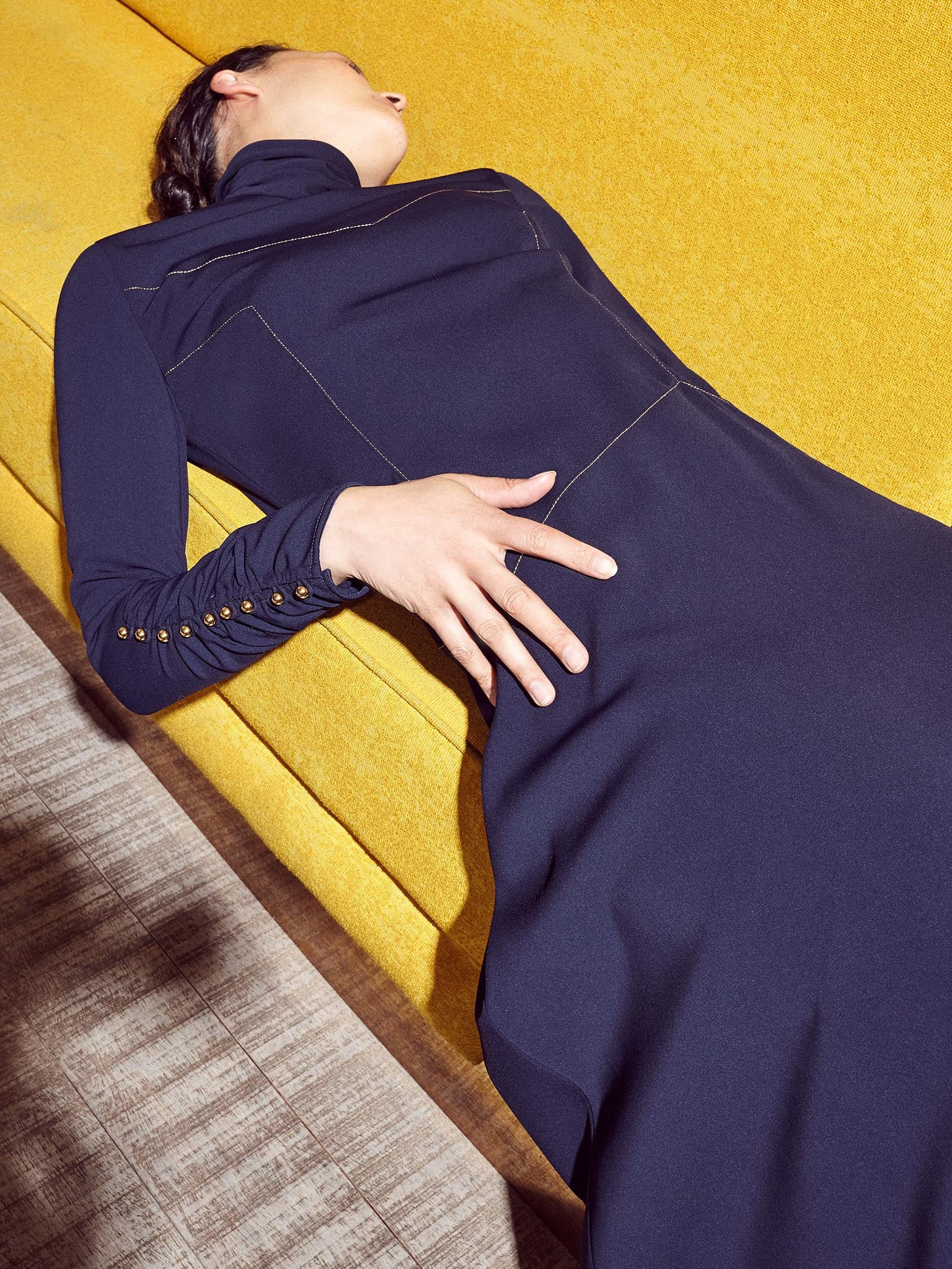 Model wearing navy women's dress with gold thread