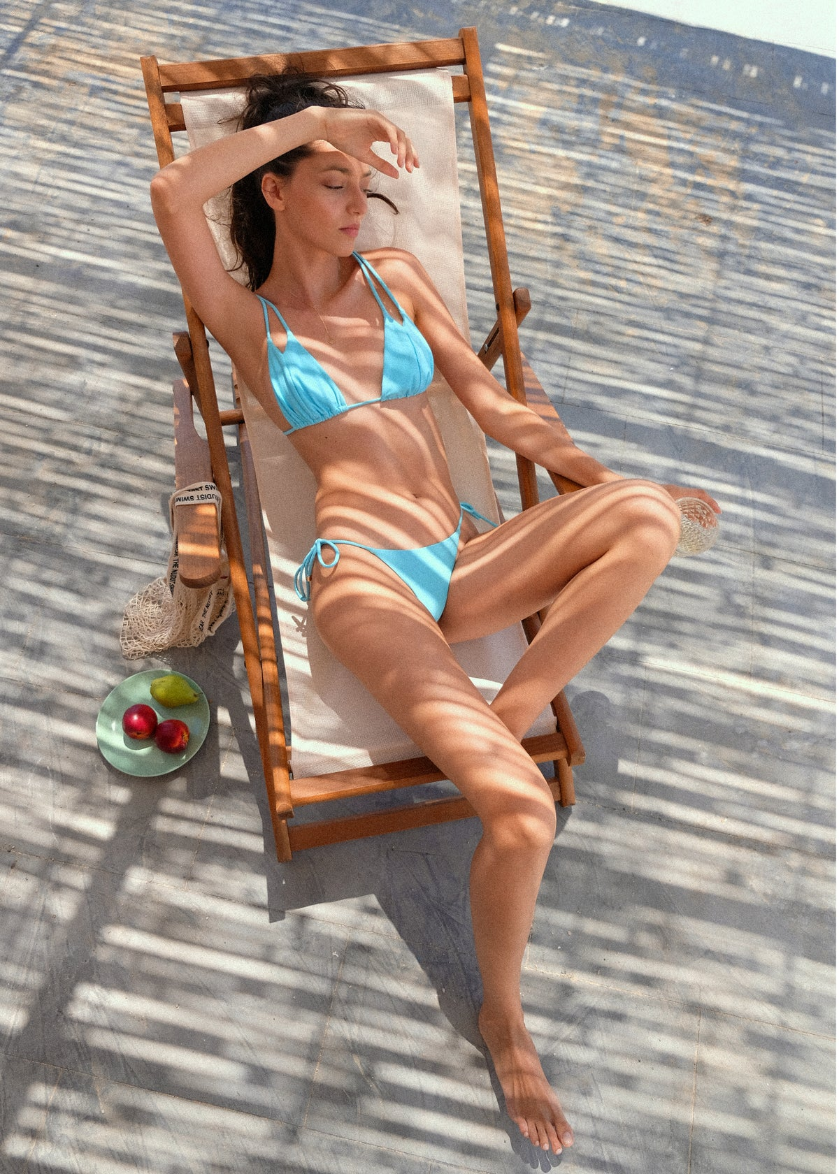 Women's blue string bikini at the beach recycled nylon by The Nudist