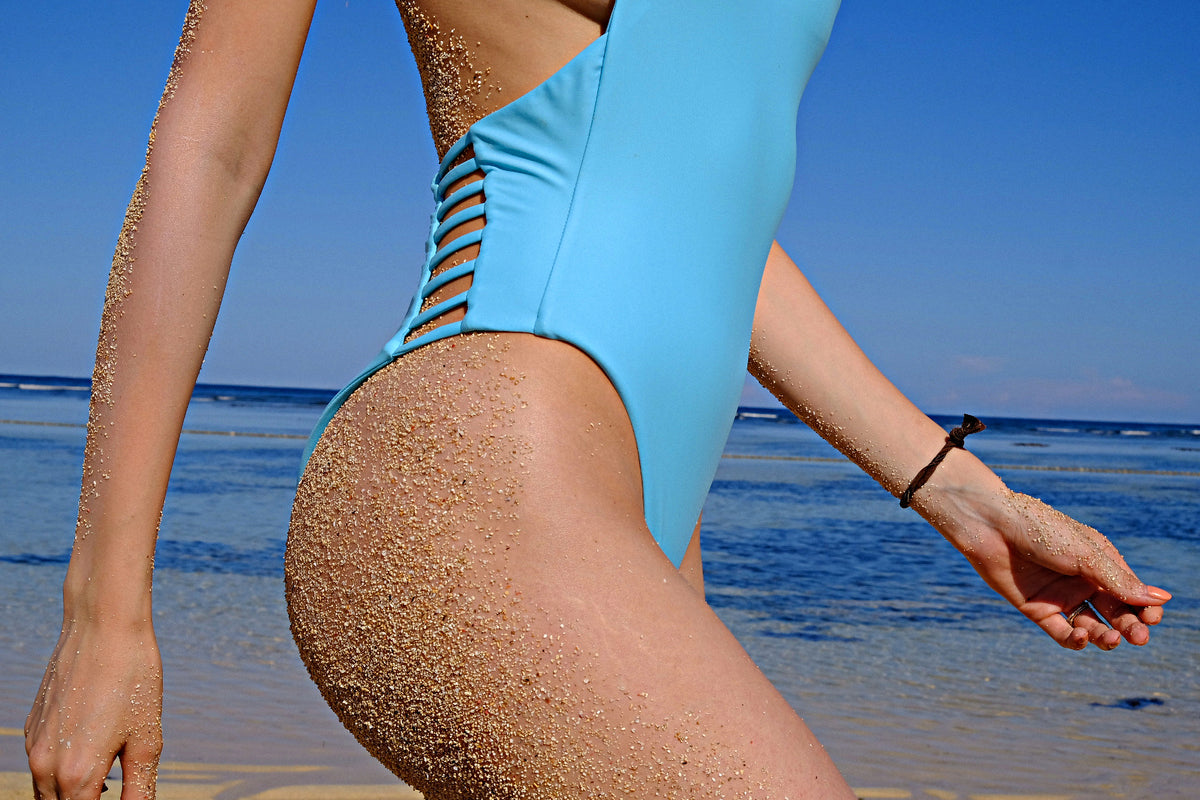 Women's blue one-piece side beach view eco-friendly swimwear by The Nudist