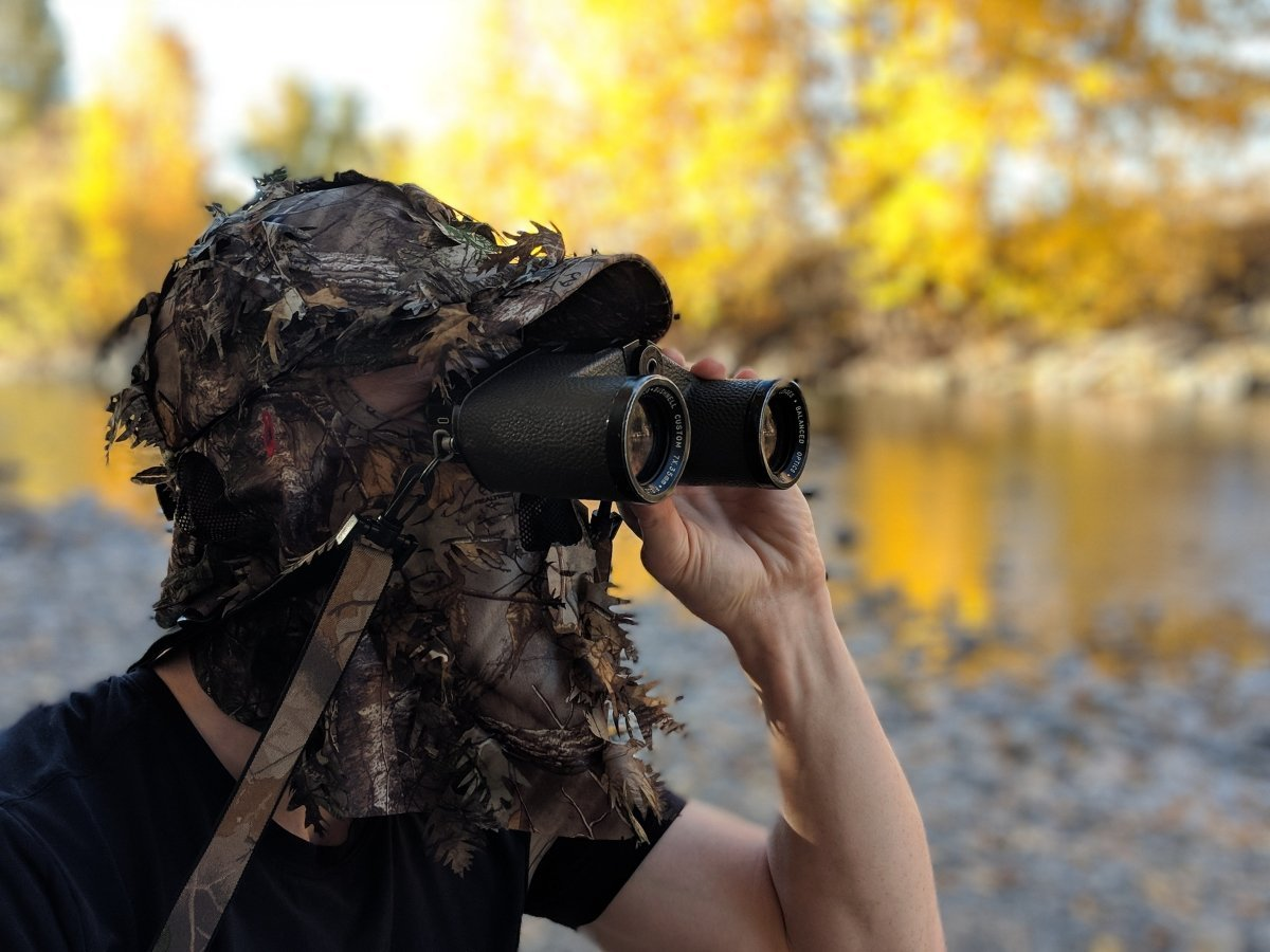 Man Wearing Realtree Xtra Leafy Camo Hat with Leafy Camo Face Mask using binoculars and he is standing by a river in a forest, Headwear by QuikCamo