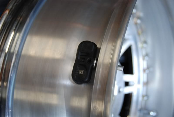 tire pressure sensor located in the pressurized pocket made by a wheel and tire