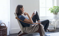 A young woman sitting in a chair using her mobile phone.