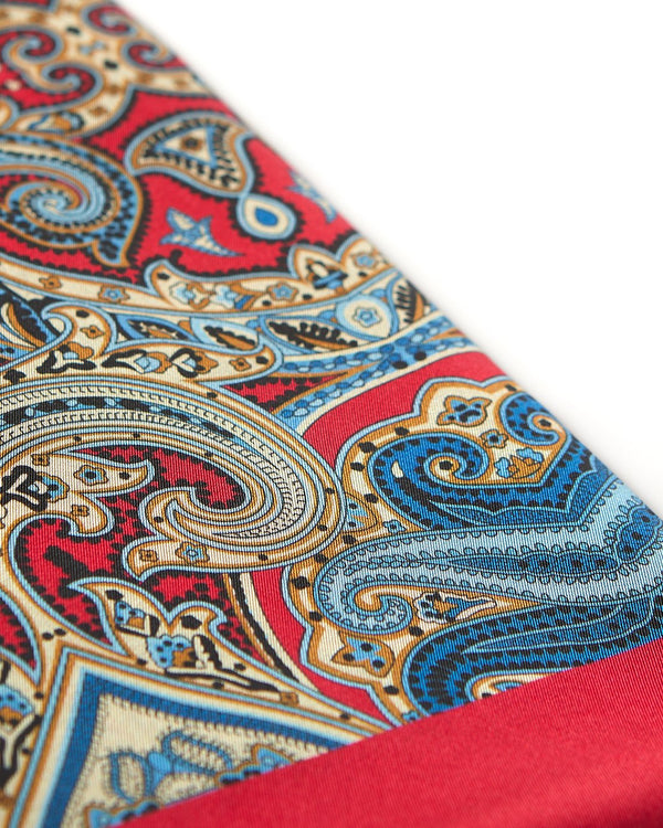 Angled view of the rich red fabric with cream and blue patterns highlighted with brown and black accents.