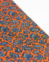 Angled view of the light and dark blue paisley patterns on the bright orange scarf.