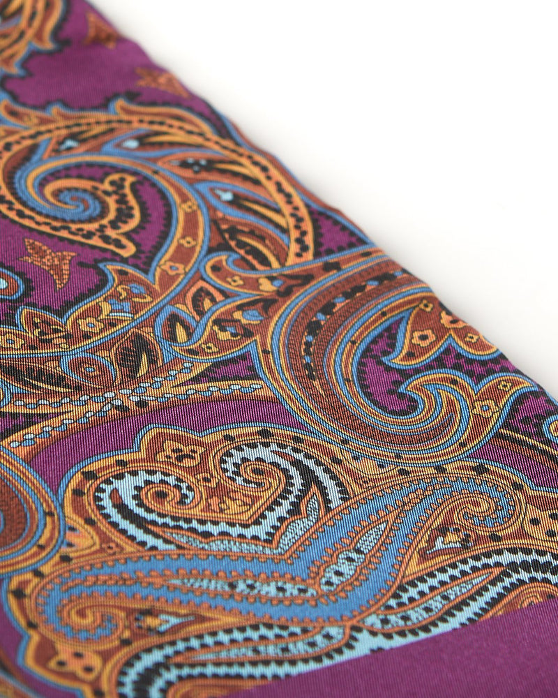 Angled closer view of the purple silk scarf with focus on the large, ornate patterns in gold and pale-blue.