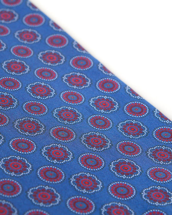 Angled view of the blue patterned 100 percent silk scarf, presenting a closer view of the small red and maroon circular and stylised floral patterns.