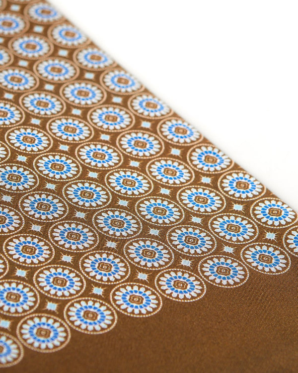 Angled view of the brown patterned 100 percent silk scarf, presenting a closer view of the small blue and white circular and stylised floral patterns.