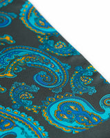 Angled closer view of the dark grey silk scarf with focus on the cyan paisley patterns and additional blue and gold patterns.