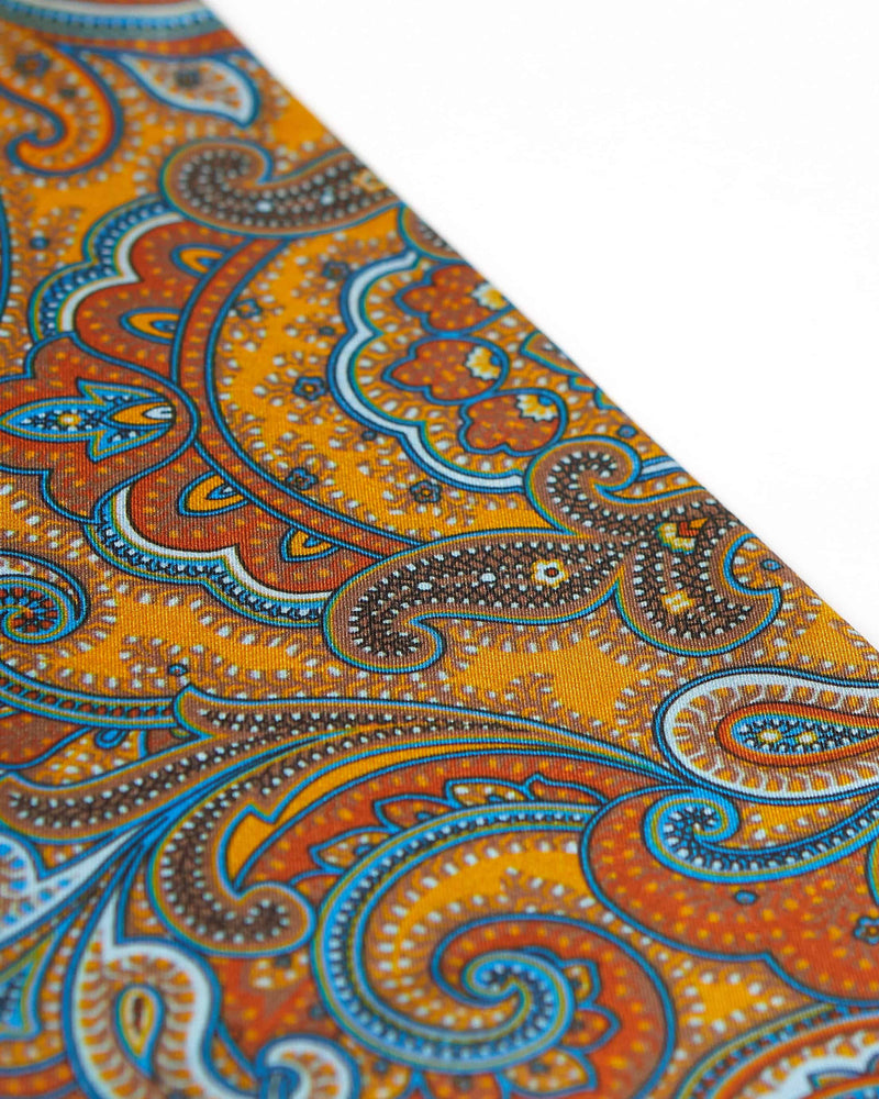 Angled view of the luxury deep gold scarf, focussing on the deep orange, light blue and brown paisley patterns.