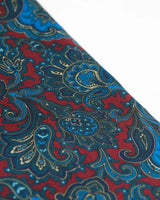 Angled view of the burgundy fabric with blue paisley patterns highlighted with lemon yellow accents.