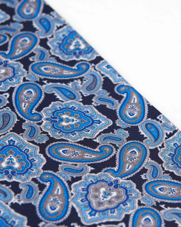 Angled view of patterned dark blue scarf, focussing on the repeated blue paisley patterns enhanced with white and grey accents.