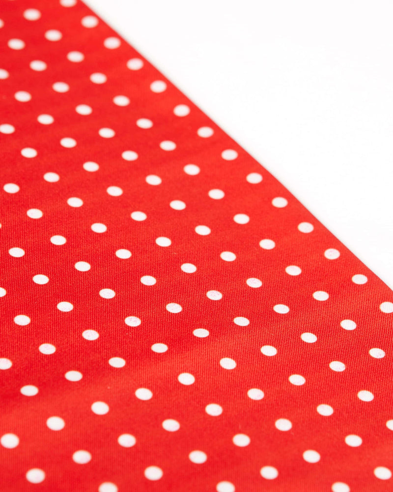 Angled view of the red and white polka dot scarf.