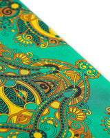Angled view of the vibrant green patterned 100 percent silk scarf, presenting a closer view of the large gold and black stylised paisley-inspired patterns.
